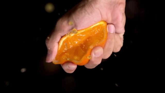 slow motion: orange squeeze on top of camera view. - orange colour stock videos & royalty-free footage