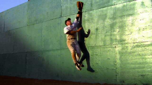slow motion outfielder jumping + missing baseball against green wall / he falls on ground - gefangen stock-videos und b-roll-filmmaterial