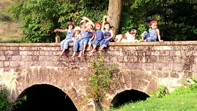 slow motion OVEREXPOSED zoom out group of children dressed in overalls sitting on bridge waving to camera