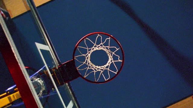 vídeos y material grabado en eventos de stock de slow motion overhead black man in red uniform dunking basketball / camera rotating - mate imagen en movimiento