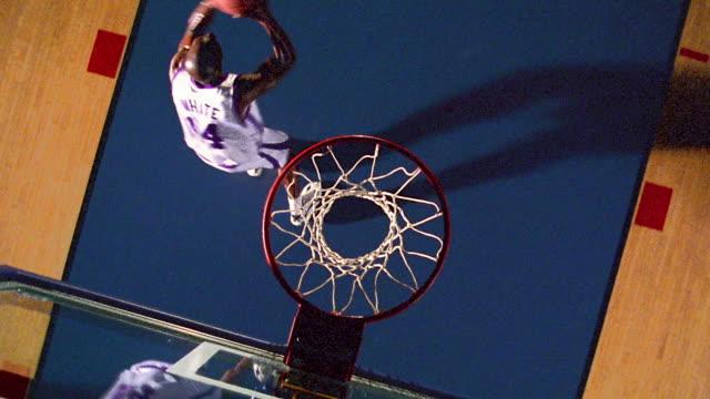 vídeos y material grabado en eventos de stock de slow motion overhead black man jumping, spinning, dunking basketball + hanging on rim / camera rotating - mate imagen en movimiento