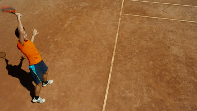 slow motion overhead of man playing tennis on clay court - forehand stock videos & royalty-free footage