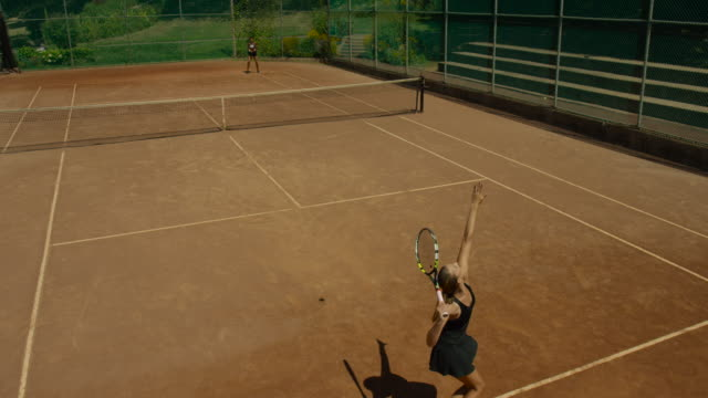 slow motion overhead shot of back of woman serving tennis ball to opponent on clay court - カーテン レース点の映像素材/bロール