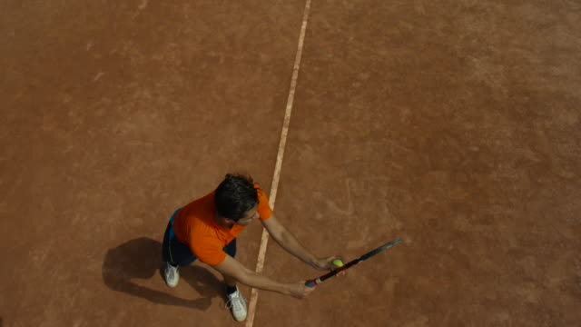 vídeos de stock e filmes b-roll de slow motion overhead shot of man bouncing tennis ball on clay court before serving - ténis calçado desportivo