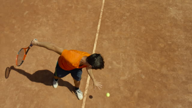 vídeos de stock e filmes b-roll de slow motion overhead shot of man bouncing tennis ball on clay court before serving - bola de ténis