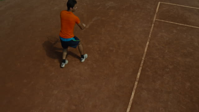 slow motion overhead shot of man making backhand return on clay tennis court - backhand bildbanksvideor och videomaterial från bakom kulisserna