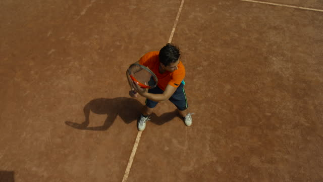 slow motion overhead shot of man making forehand return on clay tennis court - forehand stock videos & royalty-free footage