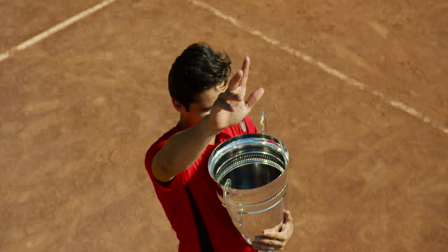 slow motion overhead shot of man on clay court with tennis trophy waving and turning - 1 minute or greater stock videos & royalty-free footage