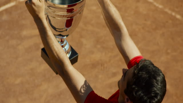 Slow motion overhead shot of man turning to left of frame and raising tennis trophy in celebration