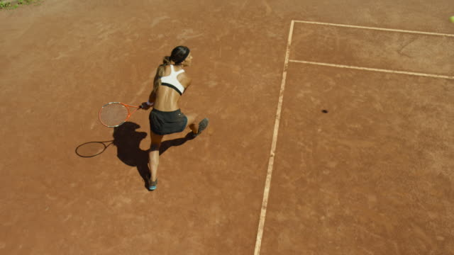 Slow motion overhead shot of woman bouncing tennis ball on clay court before serving