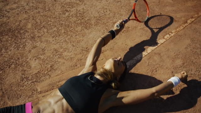 Slow motion overhead shot of woman lying on clay tennis court raising arms in victory