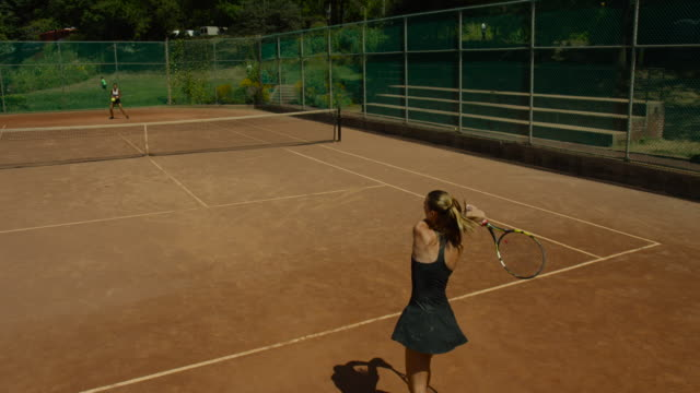 slow motion overhead shot of woman making backhand return on clay tennis court - backhand bildbanksvideor och videomaterial från bakom kulisserna