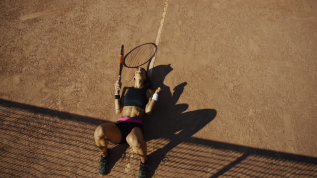 slow motion overhead shot of woman on clay tennis court dropping to the ground in victory - sports bra stock videos & royalty-free footage
