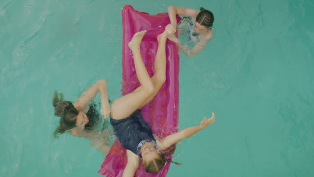 Slow motion overhead view of girls playing in swimming pool with pool raft / Cedar Hills, Utah, United States
