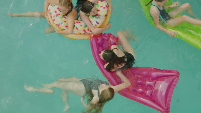 slow motion overhead view of girls swimming and playing in swimming pool / cedar hills, utah, united states - inflatable stock videos & royalty-free footage