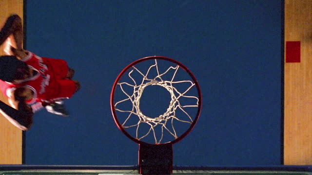 slow motion OVERHEAD zoom in Black man in red uniform dunking basketball