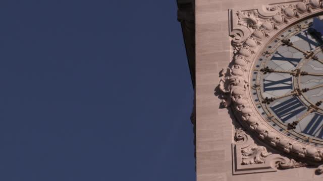 Slow motion pan across clear blue sky to reveal historical Paris Gare de Lyon Station Clock Tower Face