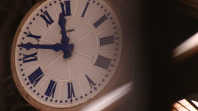 Slow motion pan across clock inside Paris Gare de Lyon station