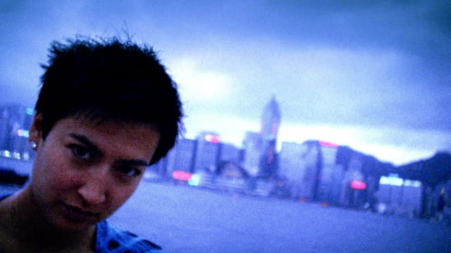 slow motion pan asian woman smiling in front of hong kong harbor with city skyline in background / hong kong - only mid adult women stock videos & royalty-free footage
