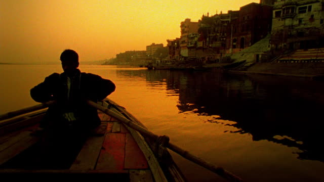 Slow motion pan boat point of view silhouetted man rowing boat on Ganges River at sunset with city in background/India