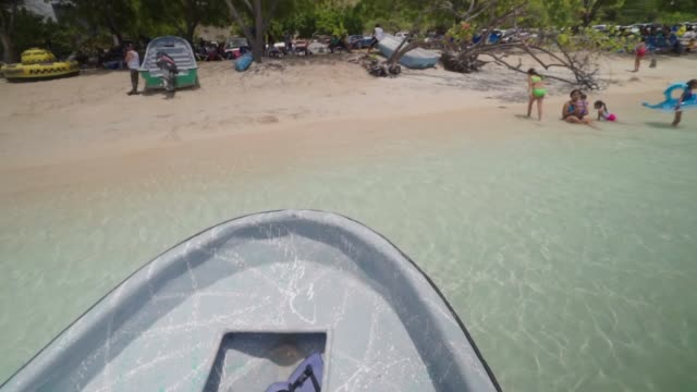 slow motion: pan down sandy beach filled with trees, families, and boats - hispaniola stock videos & royalty-free footage