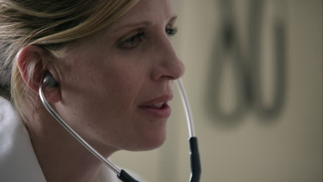 slow motion pan from doctors face to young boys as she is using stethoscope. - stetoscopio video stock e b–roll