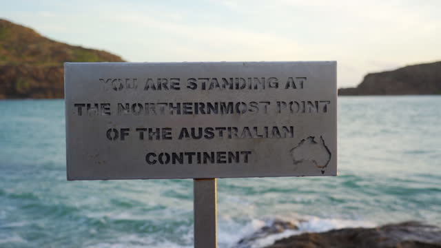 slow motion pan of a sign on the northern most point of australia, with crashing waves, coastline hills, a bright sky in the background - cape york, australia - coastline stock videos & royalty-free footage