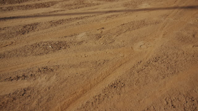 vidéos et rushes de slow motion pan of clay tennis court with man's feet sliding through - soil