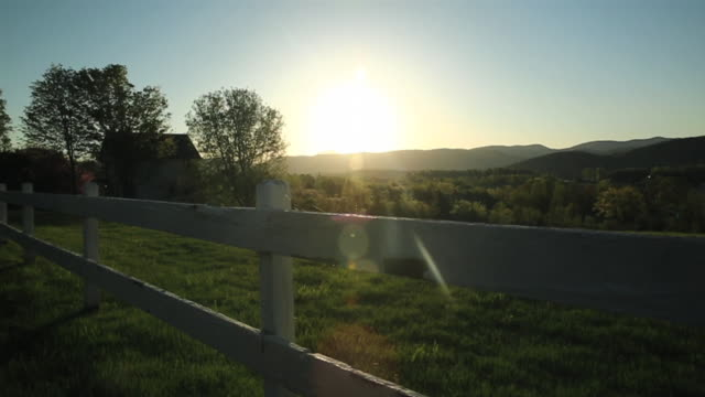 Slow motion pan of fence, barn, mountains and the sun before sunset