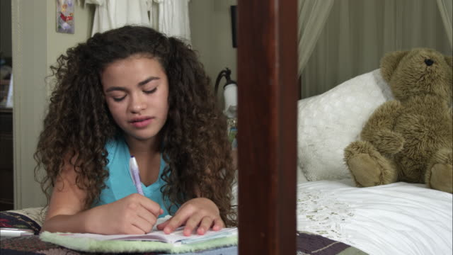 slow motion pan of girl writing in diary then looking up to smile. - diary stock videos & royalty-free footage