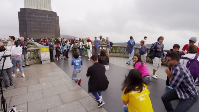 slow motion pan of people atop corcovado mountain moving in unison. - male likeness stock videos & royalty-free footage