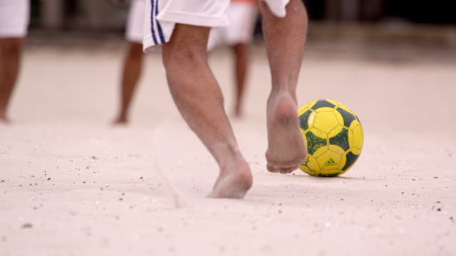 Slow motion pan of soccer game at Tavares Bastos Favela in Rio de Janeiro, Brazil