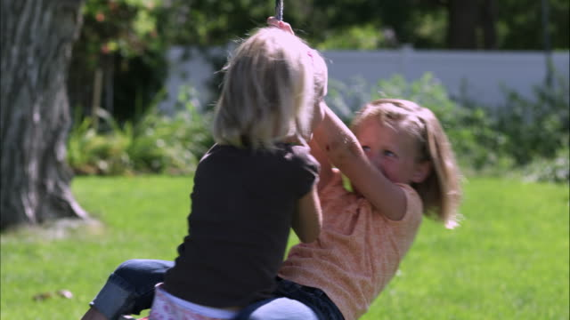 Slow motion pan of two girls sharing a tree swing