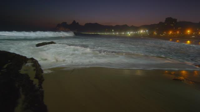 Slow motion, pan right of waves crashing against Ipanema beach at night