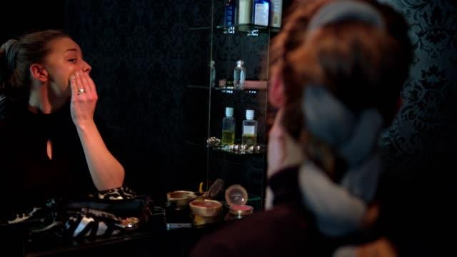 vidéos et rushes de slow motion pan shot d'une jeune femme faisant son maquillage appliquer la fondation - pinceau à blush