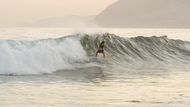 vídeos de stock, filmes e b-roll de slow motion pan shot of surfer, with large buildings and mountains in background - arrebentação