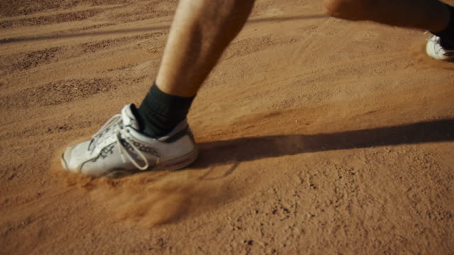 slow motion pan to left of clay tennis court with man's legs sliding into frame - tennis video stock e b–roll