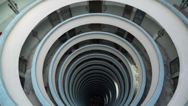 slow motion: pan up from center of circular building - steel stock videos & royalty-free footage