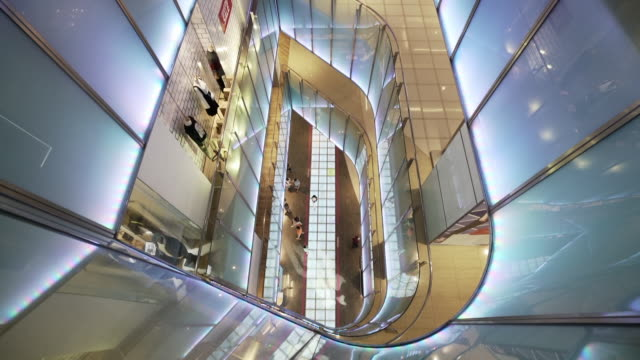 slow motion: pan up of illuminated glass interior of building - diminishing perspective stock videos & royalty-free footage