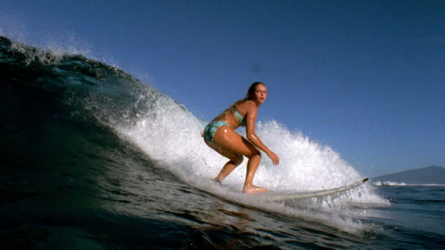 Slow motion pan wide shot female surfer riding wave / Tahiti