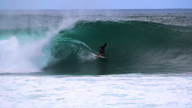 slow motion panning a surfer catching and riding a large crashing barrel wave, with bright blue sky and white surf spray - oahu, hawaii - using a paddle stock videos & royalty-free footage