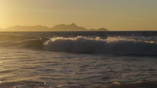 vídeos de stock, filmes e b-roll de slow motion: panning along breaking wave in ocean at sunrise - footpath
