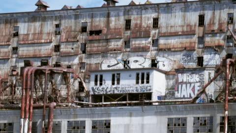 vidéos et rushes de slow motion: panning along old rusted warehouse with graffiti - délabré