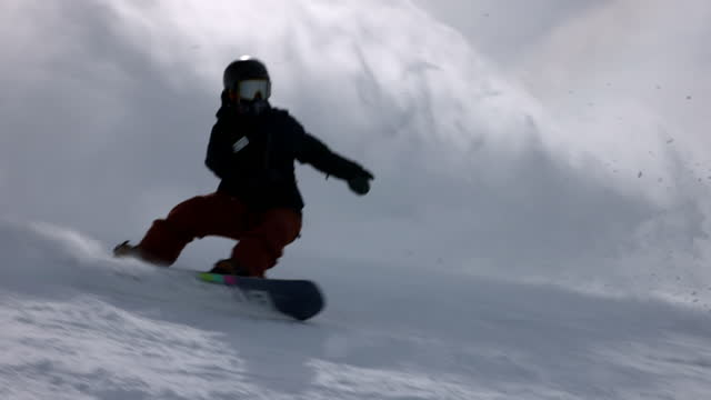 slow motion panning shot of adventurous person splashing while snowboarding over mountain on sunny day during vacation - mammoth lakes, california - スノーボード点の映像素材/bロール