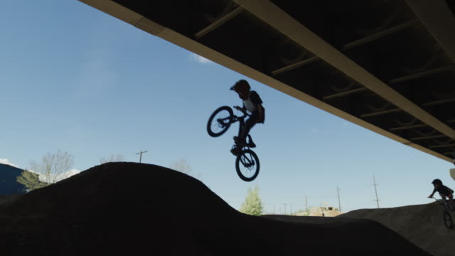slow motion panning shot of approaching boys jumping hills on bicycles at bike park / salt lake city, utah, united states - bmx stock-videos und b-roll-filmmaterial