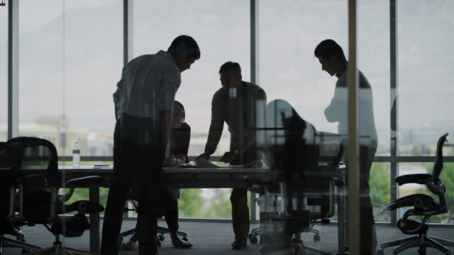 slow motion panning shot of business people examining blueprints in meeting / pleasant grove, utah, united states - ufficio video stock e b–roll
