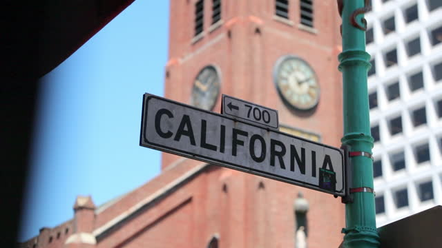 slow motion panning shot of california street sign against clock tower in city - san francisco, california - capital letter stock videos & royalty-free footage