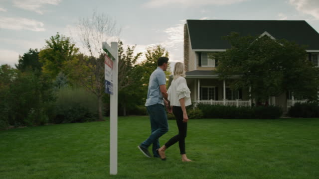 slow motion panning shot of couple hugging on lawn of house for sale / pleasant grove, utah, united states - full length点の映像素材/bロール