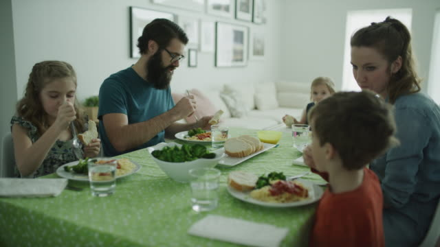 slow motion panning shot of family eating at dinner table / lehi, utah, united states - family with three children stock videos & royalty-free footage