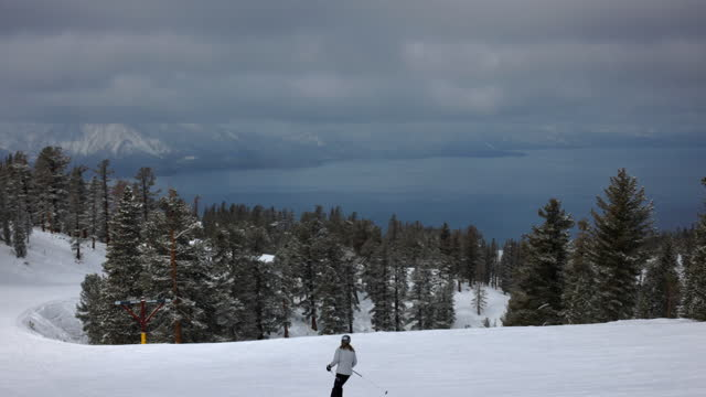 stockvideo's en b-roll-footage met slow motion panning shot of female tourists skiing over snowy landscape by lake on sunny day - lake tahoe, california - sunny